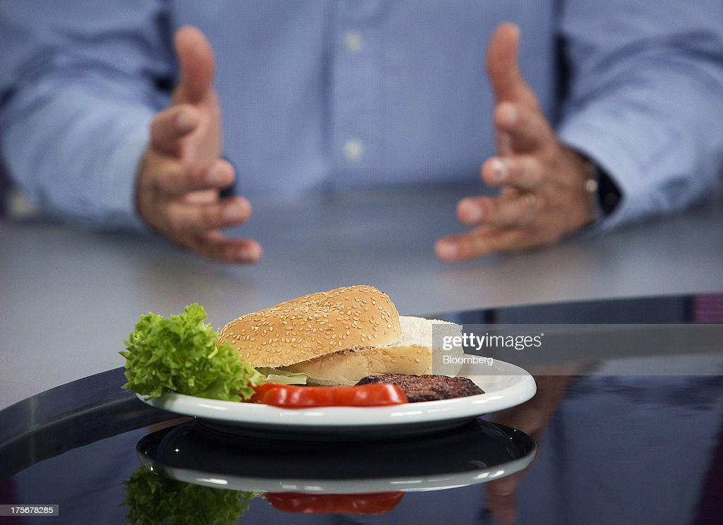 The world's first beef burger created from stem cells harvested from a living cow sits on a plate with a bun, lettuce and tomato on a plate in front of Mark Post, a Dutch scientist, during a Bloomberg Television interview in London, U.K., on Tuesday, Aug. 6, 2013. The 5-ounce burger, which cost more than 250,000 euros ($332,000) to produce, was developed by Post of Maastricht University with funding from Google co-founder Sergey Brin. Photographer: Simon Dawson/Bloomberg via Getty Images