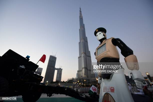 TOPSHOT The world's first operational police robot stands at attention as they prepare a military cannon to fire to mark sunset and the end of the...