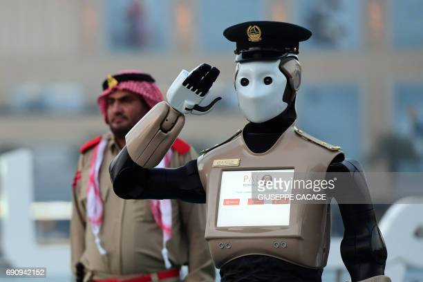 The world's first operational police robot stands at attention as they prepare a military cannon to fire to mark sunset and the end of the fasting...