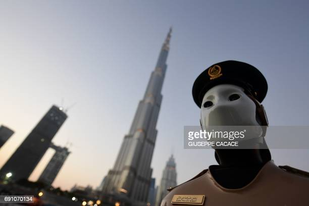 TOPSHOT The world's first operational police robot stands to attention near the Burj Khalifa in Downtown Dubai on May 31 as a military cannon is...