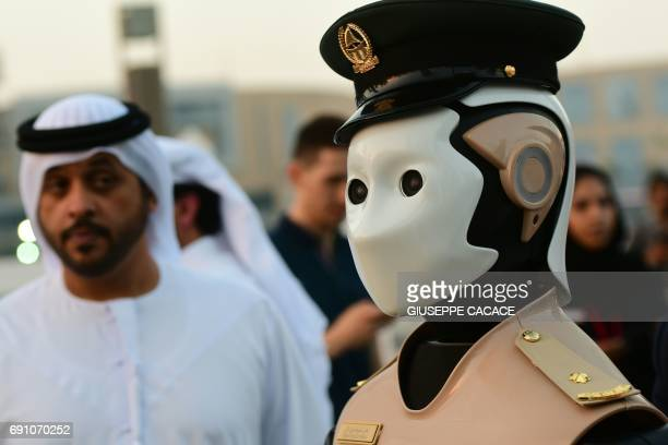 The world's first operational police robot stands to attention near the Burj Khalifa in Downtown Dubai on May 31 as a military cannon is prepared to...