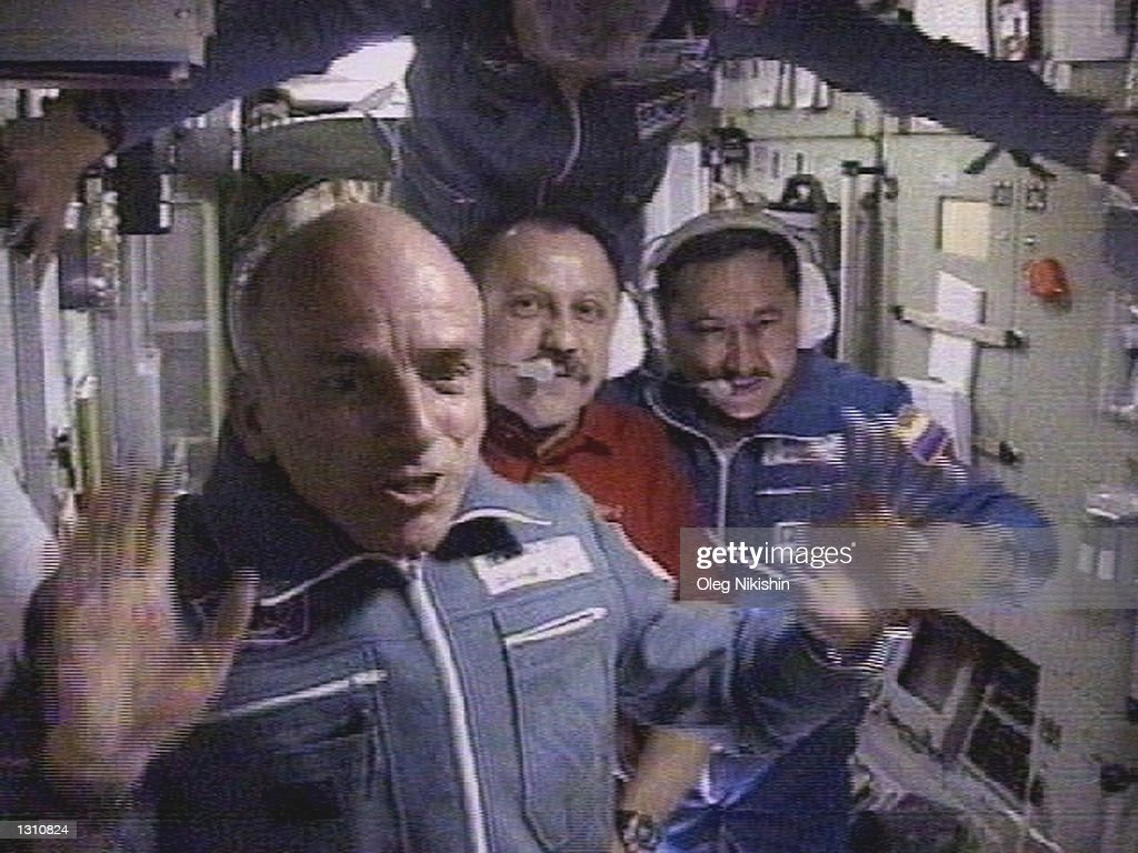The worlds first space tourist Dennis Tito waves in front of the International Space Station crew shortly after his arrival to the station April 30, 2001 in this image from television. In the background are space station commander Yuri Usachev, center, bottom, Russian cosmonauts Talgat Musabayev, right, and Yuri Baturin, center, top. Tito is paying as much as $20 million for this adventure of a lifetime. (Photo by RTV/Oleg Nakishin/Newsmakers