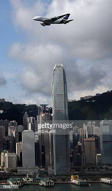 The world's largest passenger plane airbus A380 flies over Victoria harbour in Hong Kong with the territory's tallest landmark the 1400foot...