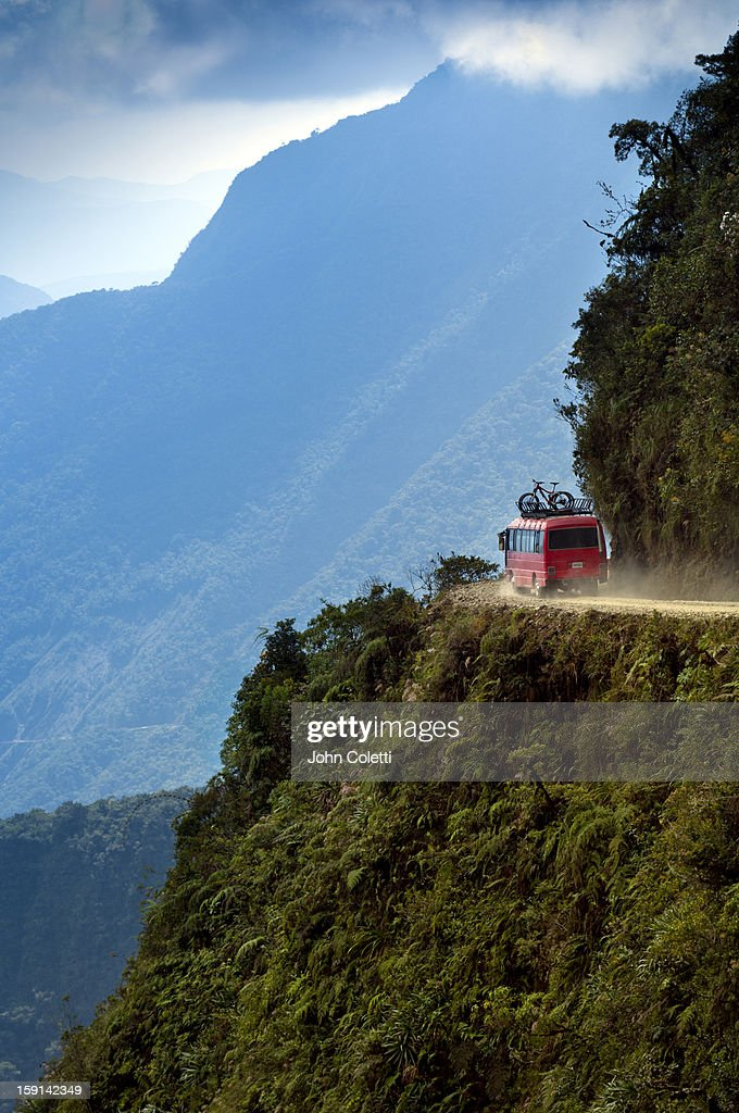 A support van for mountain bicyclists makes its way around a hairpin turn on The World's Most Dangerous Road or The Road Of Death, a 43 mile mountain dirt road that connects La Paz to the town of Coroico in the Yungas jungles of Bolivia. The road is known for its extreme dropoffs, narrow widths and turns, and has been responsible for many accidents. It is now a popular tourist destination for mountain bikers.
