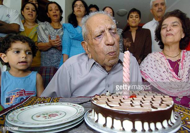 The world's oldestknown living Olympic medal winner Pakistan's Feroze Khan blows out the candle on a cake as he celebrates his100th birthday with...