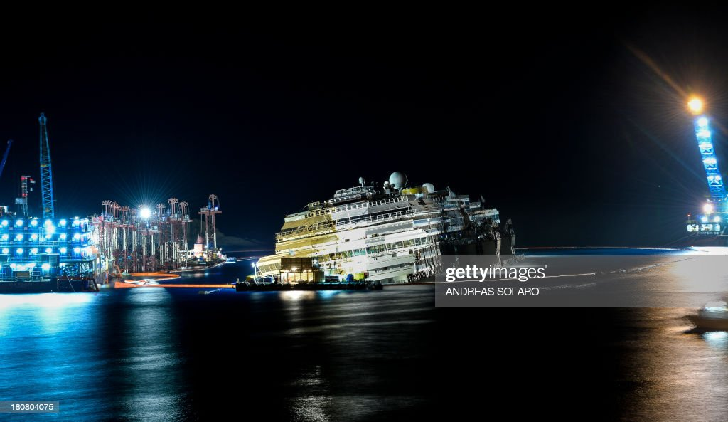The wreck of Italy's Costa Concordia cruise ship begins to emerge from water on September 17, 2013 near the harbour of Giglio Porto. Salvage workers attempt to raise the cruise ship today and tonight, in the largest and most expensive maritime salvage operation in history, so-called 'parbuckling', rotating the ship by a series of cables and hydraulic machines. Thirty-two people died when the ship, with 4,200 passengers onboard, hit rocks and ran aground off the island of Giglio on January 2012. AFP PHOTO / ANDREAS SOLARO