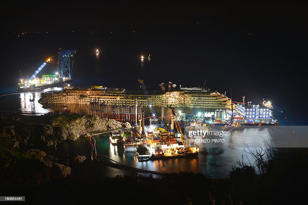 The wreck of Italy's Costa Concordia cruise ship begins to emerge from water on September 17, 2013 near the harbour of Giglio Porto. Salvage operators in Italy lifted the Costa Concordia cruise ship upright from its watery grave off the island of Giglio on Tuesday in the biggest ever project of its kind.