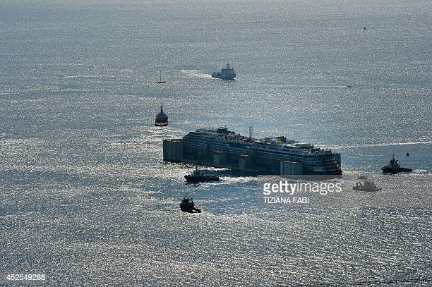 The wreck of the Costa Concordia cruise ship is carried away in front of the harbour of Isola del Giglio after it was refloated using air tanks...