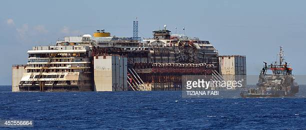 The wreck of the Costa Concordia cruise ship is towed away in front of the harbour of Isola del Giglio after it was refloated using air tanks...