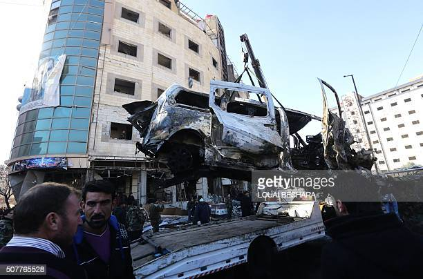 The wreckage of a vehicle is being loaded on a truck as Syrian progovernment forces and residents gather at the site of suicide bombings in the area...