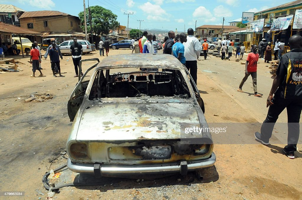 The wreckage of car is pictured on July 6 2015 in the central Nigerian city of Jos Plateau State the day after a twin bomb blasts that killed at...