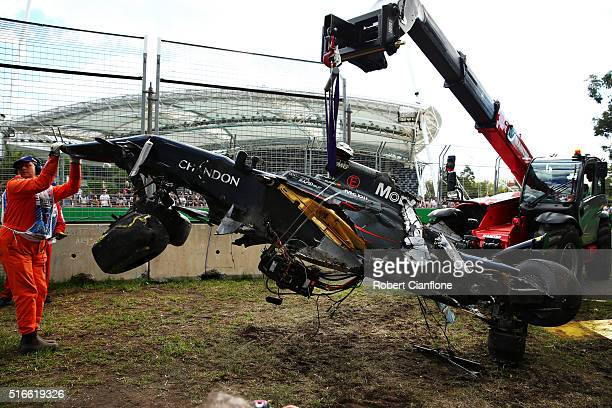 The wreckage of Fernando Alonso of Spain and McLaren Honda gets moved to the side of the track during the Australian Formula One Grand Prix at Albert...