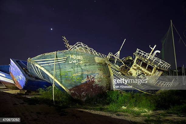 The wreckage of former migrant ships are lit by passing cars at twilight on April 24 2015 in Lampedusa Italy Migrants continue to arrive in Lampedusa...