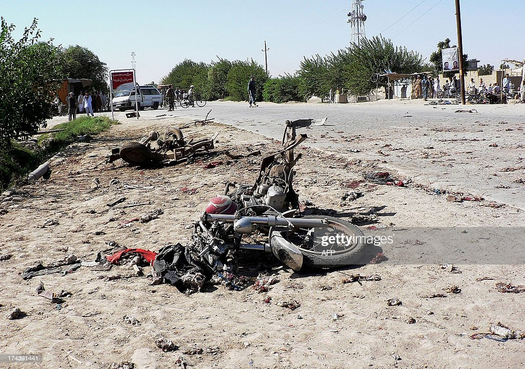 The wreckage of motorcycle lies at the site of a bomb blast in Aqcha district in the northern Afghan province of Jawzjan on July 25, 2013. An explosion killed four including one policeman and wounded eleven civilians, officials said on July 25. AFP PHOTO/ Farshad Usyan