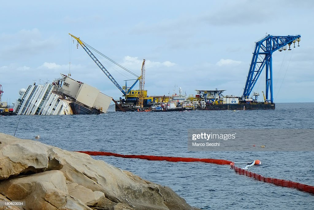 The wreckage of the Costa Concordia is surrounded by a floating barrier to contain possible spillage and pollution on September 13, 2013 in Isola del Giglio, Italy. Work is expected to begin on September 16 to right the stricken Costa Concordia vessel. If the operation is successful, it will then be towed away and scrapped.
