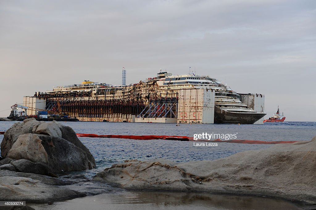 The wrecked cruise ship Costa Concordia Costa Concordia sits in the water a few hours before the maneuvers and departure of the ship form the island on July 22, 2014 in Isola del Giglio, Italy. Technicians are preparing to start towing the ship to the port of Genoa for dismantling on Wednesday, July 23.