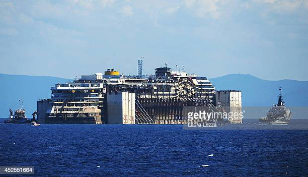 The wrecked cruise ship Costa Concordia is towed by tugs from Giglio after being refloated on July 23 2014 in Isola del Giglio Italy The ship is...