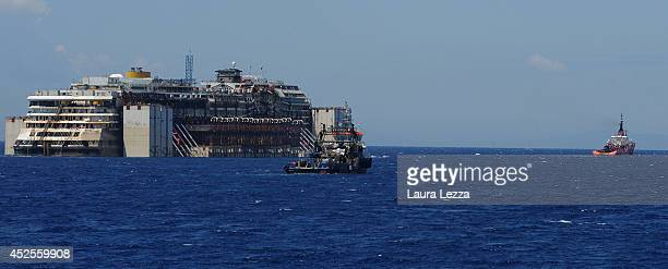 The wrecked cruise ship Costa Concordia is towed by tugs from Giglio in the open sea after being refloated on July 23 2014 in Isola del Giglio Italy...