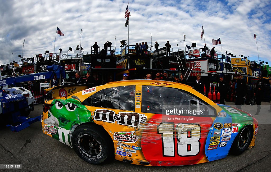 The wrecked #18 M&M's Toyota of Kyle Busch is towed in the garage area after an on track incident during practice for the NASCAR Sprint Cup Series 13th Annual Hollywood Casino 400 at Kansas Speedway on October 5, 2013 in Kansas City, Kansas.