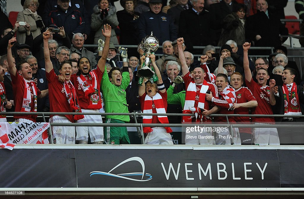 The Wrexham captain Dean Keates lifts the FA Trophy as his team mates celebrate their victory in the FA Trophy Final between Wrexham and Grimsby Town at Wembley Stadium on March 24, 2013 in London, England.
