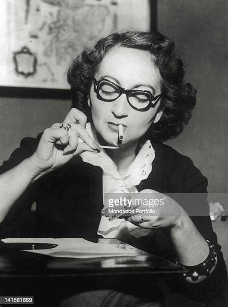 The writer Alba de CTspedes y Bertini photographed while lighting a cigarette 1950s