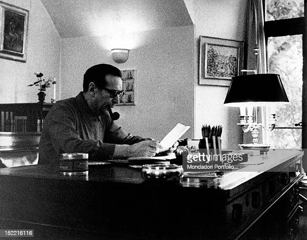 The writer Georges Simenon in his studio at his castle smoking a pipe and looking at a sheet of paper in front of him Echandes Switzerland September...