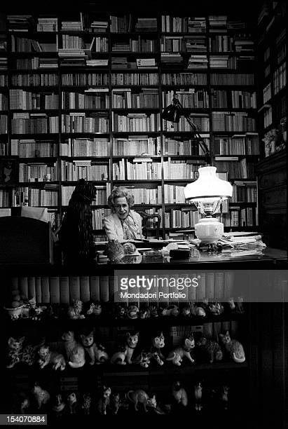 The writer Gianna Manzini posing sitting at her desk in the stydy of her home among books and cat statuettes Rome 1971