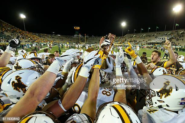 The Wyoming Cowboys celebrate with The Bronze Boot after defeating Colorado State Rams 3817in the border war at Sonny Lubick Field at Hughes Stadium...