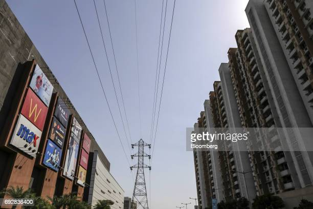 The Xperia Mall left and residential apartment buildings right stand either side of power lines in Palava City on the outskirts of Mumbai India on...
