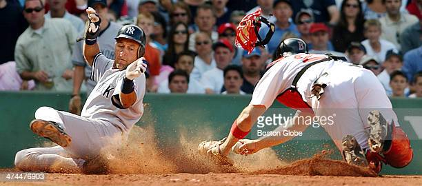 The Yankees' Derek Jeter left slides home in a sea of clay as Red Sox catcher Doug Mirabelli right is late with the tag and loses his mask Jeter...