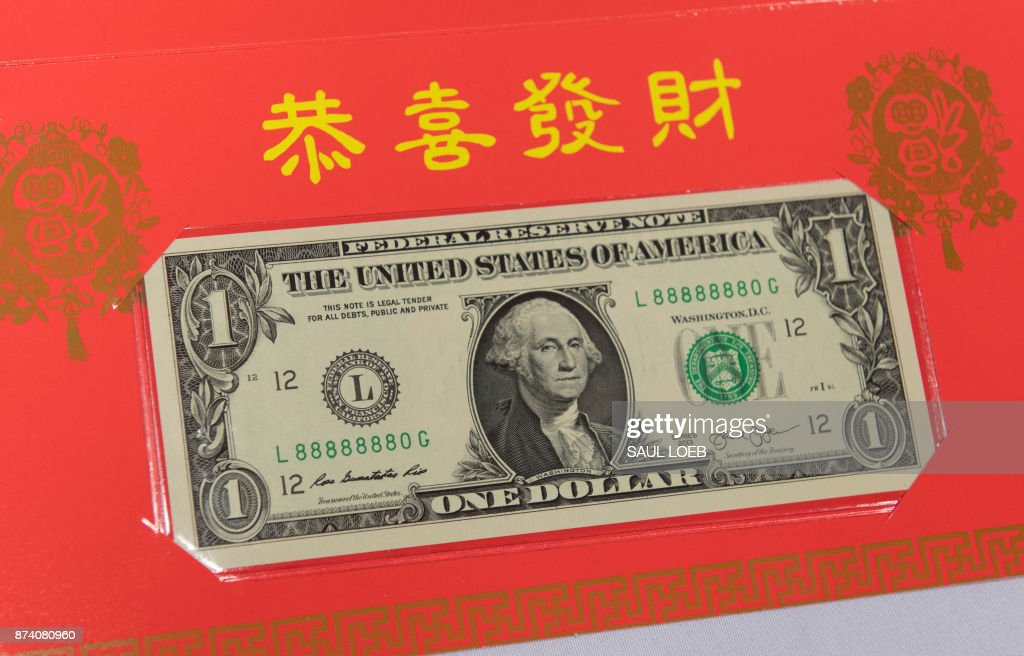 The Year of the Dog 2018 product in celebration of the Chinese Lunar New Year, featuring a $1 Federal Reserve note with a serial number beginning with '8888', is seen during a press conference for its unveiling at the Bureau of Engraving and Printing in Washington, DC, November 14, 2017. /
