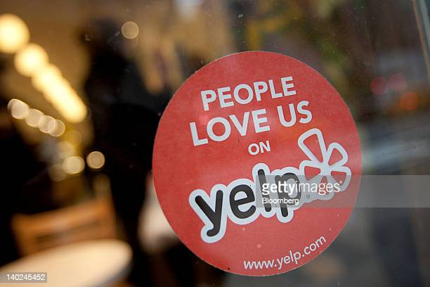 The Yelp Inc logo is displayed in the window of a restaurant in New York US on Thursday March 1 2012 Yelp Inc the site that lets users review...