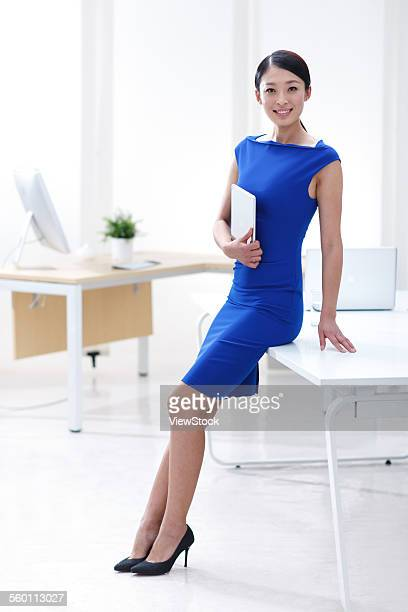 The young business women took the tablet computer leaned on the desk