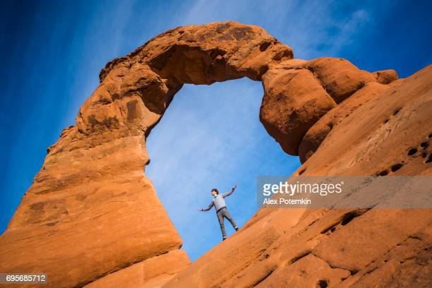 The young happy man, hiker, feels freedom under the Delicate Arch at the sunset. Arches National Monument, Utah, USA