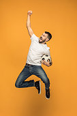 The young man as soccer football player jumping and kicking the ball at studio on a yellow background. Jumping footballer in a combat kick. Football fan and world championship concept. Human emotions