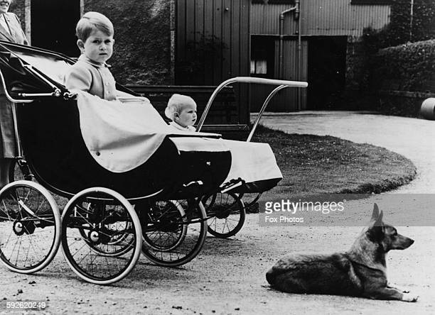 The young Prince Charles and Princess Anne sitting in their prams next to one of their mother's corgis listening to the music of the Argyll and...