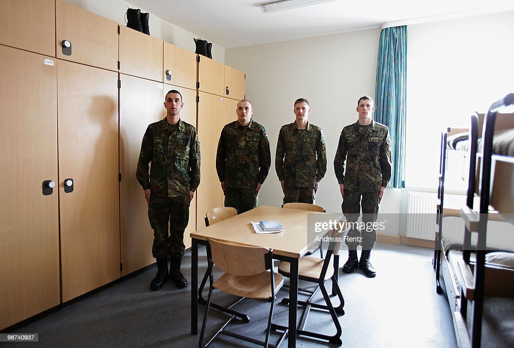 The young recruits Witzig Koenig Schirmer and Gaburek of the German Bundeswehr stand at attention in an honour guard in their living room during...
