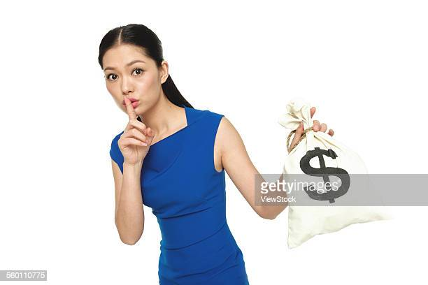 The young woman index finger on the lips and took the purse