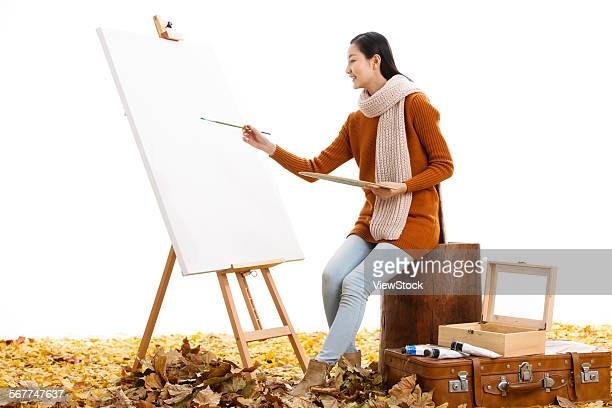 The young woman painting outdoors