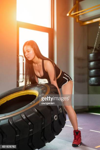 The young women moving a car tire at the gym