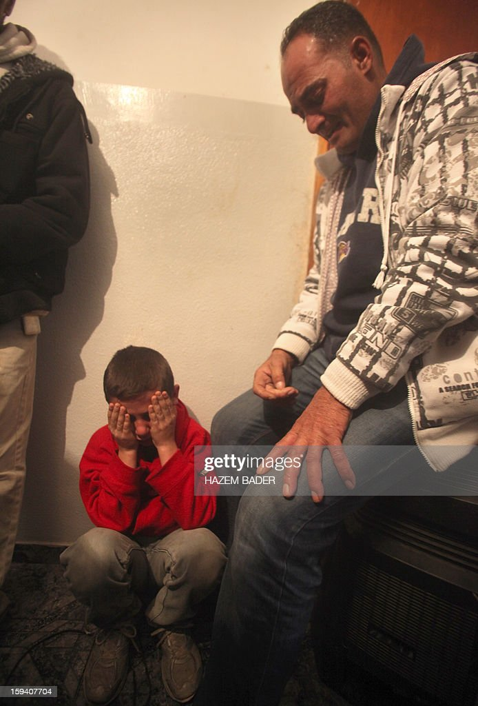 The younger brother (C) of Odai Darwish, 21, grieves during his brother's funeral on January 13, 2013, in the village of Duma, the day after he was shot dead by Israeli soldiers as he tried to sneak from the occupied West Bank, south of the city of Hebron, into the Jewish State to get to a job, Palestinian officials told AFP. The Israeli military confirmed that a border shooting took place but did not know the extent of the man's injuries.