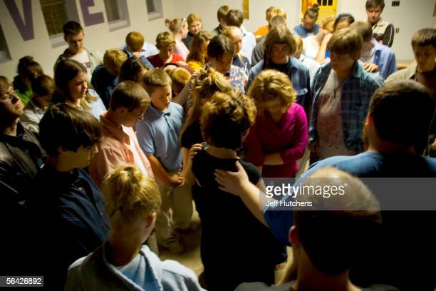 The youth group prays to bless a missionary before she goes to serve abroad during the evening service for junior high and high school students...