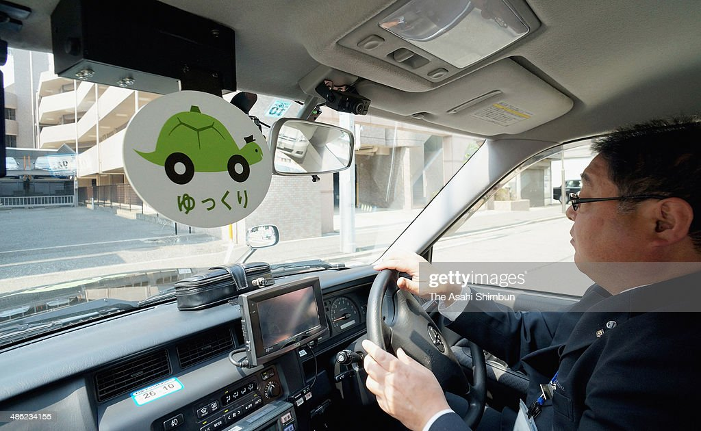 The 'Yukkuri (slow)' plate flips down near the front window when slow service is preferred in the turtle taxi on April 17, 2014 in Yokohama, Kanagawa, Japan. Sanwa Kotsu began the unique service it dubbed 'Turtle Taxi' in December 2013. Ten of the companies' 500 cabs were given that designation. The drivers are told to accelerate and decelerate carefully as well as restrain the centrifugal forces on passengers when making turns. The service has been welcomed by senior citizens and pregnant women. In the three months since the Turtle Taxis started, the company has recorded a 15-percent increase in the number of telephone requests specifically for one.