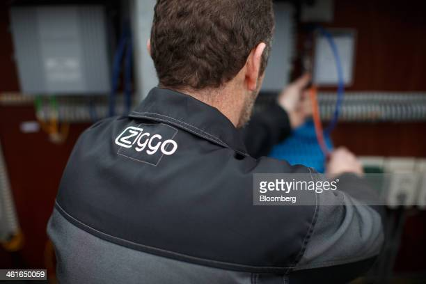 The Ziggo NV company logo sits on an internet cable technician's jacket as he carries out maintenance work on a fiber optic internet cable box in...