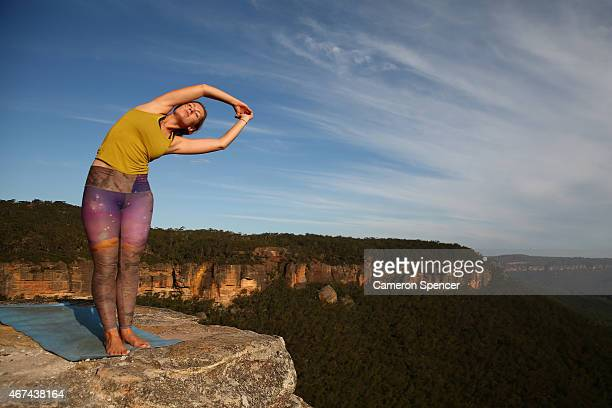 Thea Bainbridge of England practices yoga on the cliffs at Corroboree Walls in Mount Victoria on March 7 2015 in the Blue Mountains Australia On...