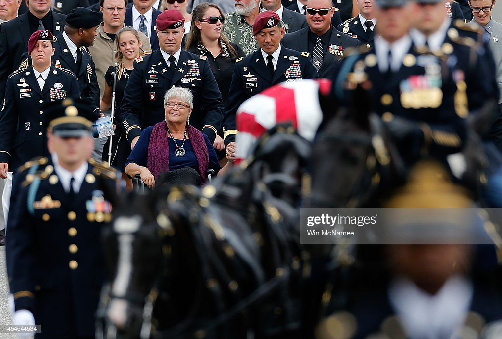 Thea Kurz (C), the mother of Sgt. First Class Matthew Leggett, joins a procession of family and friends at the burial service for her son at Arlington National Cemetery September 3, 2014 in Arlington, Virginia. Leggett, a paratrooper stationed at Ft. Bragg who received the Bronze Star Medal and Purple Heart, was killed in action on August 20, 2014 while serving his third tour of Afghanistan.