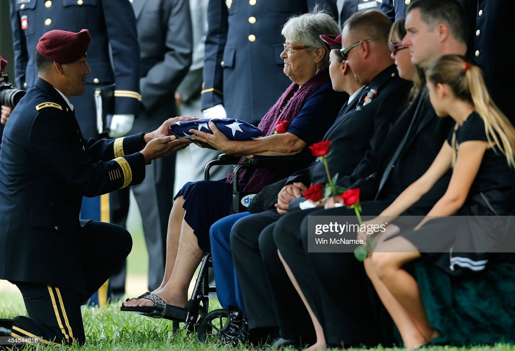 Thea Kurz, the mother of Sgt. First Class Matthew Leggett, receives an American flag from Army Major Gen. Clarence Chinn during the burial service for her son at Arlington National Cemetery September 3, 2014 in Arlington, Virginia. Leggett, a paratrooper stationed at Ft. Bragg who received the Bronze Star Medal and Purple Heart, was killed in action on August 20, 2014 while serving his third tour of Afghanistan.