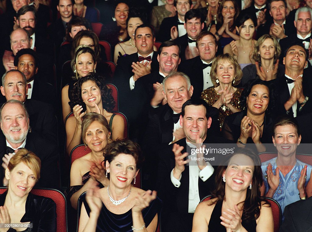 Theater audience in formal attire, applauding, portrait