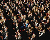 Theater audience wearing formal attire, applauding, overhead view
