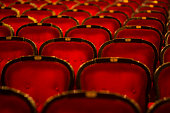 Numbered theater chairs upholstered in burgundy